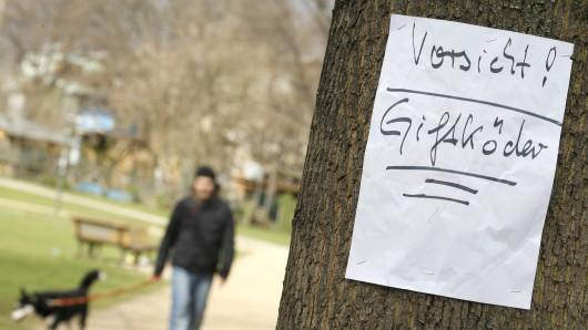 ARCHIV - ILLUSTRATION- Ein Zettel warnt am 30.03.2012 in einem Park in Berlin vor ausgelegten Giftködern. Foto: Florian Schuh/dpa (zu dpa-KORR Die Rache der Hundehasser -Mehr Giftköder in Berlin? vom 20.03.2016) +++(c) dpa - Bildfunk+++