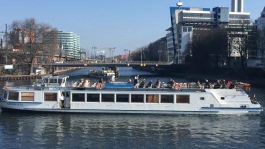 Passagiere eines Ausflugsschiffes auf der Spree genießen die Sonne