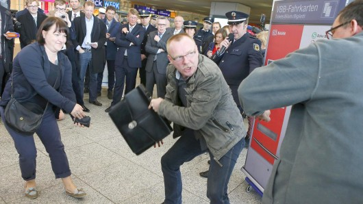 Innenminister de Maizière (hinten, rechts) schaut am Montag am Ostbahnhof einer Übung für die Bundespolizisten gegen Taschendiebe zu