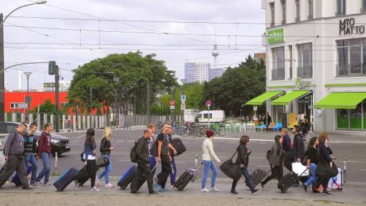 Touristen mit Rollkoffern im Bezirk Friedrichshain-Kreuzberg: Der Kiez an der Warschauer und Revaler Straße zieht Reisende an