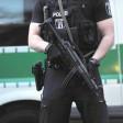 Ein Polizist mit Maschinenpistole  am Abend vor einem Haus an der Sickingenstraße in Moabit. Die Polizei überprüfte zahlreiche Rocker.