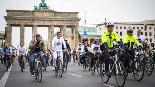 Zahlreiche, in weiß gekleidete Fahrradfahrer versammeln sich am 18.05.2016 vor dem Brandenburger Tor in Berlin, um zu einer Gedenkfahrt aufzubrechen, die an verunglückte Radfahrer erinnern soll. Foto: Sophia Kembowski/dpa +++(c) dpa - Bildfunk+++