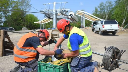 Arbeiter spleißen auf der Baustelle der Internationalen Gartenausstellung (IGA) am Seilzug für die Seilbahn. In 30 Metern Höhe sollen Gondeln die 1,5 Kilometer lange Strecke ab dem Frühling 2017 entlang fahren