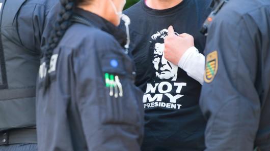 Ein Mann trägt ein T-Shirt mit der Abbildung von Gauck mit der Aufschrift Not my President während des Besuches des Bundespräsidenten