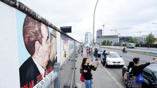 """Touristen vor dem Gemälde """"Bruderkuss zwischen Leonid Breschnew und Erich Honecker"""""""