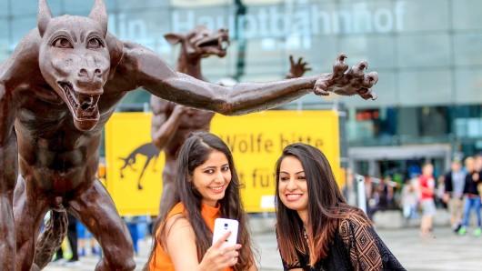"""Die Berlin-Besucherinnen Neha (l.) und Sakshi aus Indien fotografieren sich vor den Skulpturen der neuen Ausstellung """"Die Wölfe sind zurücj"""" auf dem Washingtonplatz vor dem Hauptbahnhof. Bis zum 16.08.2016 stehen die Figuren auf dem Platz und können besichtigt werden"""