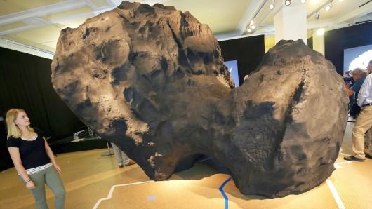 Eine Besucherin betrachtet im Naturkundemuseum in Berlin ein Modell des Kometen Churyumov-Gerasimenko im Maßstab 1:1000, der als Größenvergleich auf dem Stadtplan von Berlin-Mitte steht.