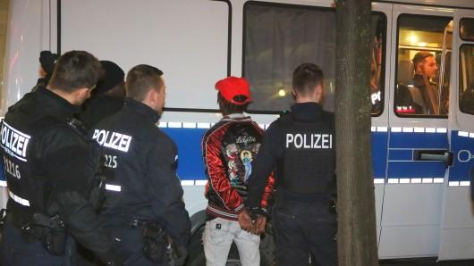 Polizisten mit einem der festgenommenen Männer