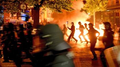 Polizisten laufen in Hamburg im Schanzenviertel an einer brennenden Barrikade vor der Roten Flora entlang