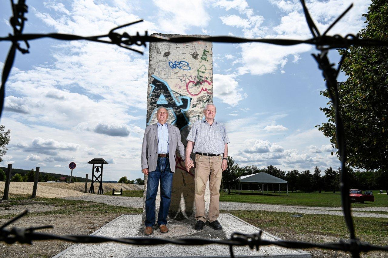 Die Grenzer Árpád Bella (links) und Johann Göltl vor einem Stück Berliner Mauer an der Gedenkstätte für das Paneuropäische Picknick. Jetzt stehen sie dort Hand in Hand.