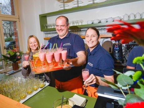 """Yvette Geßler-Fahr (v.l.), Rene Will und Stephanie Kießling servieren die ersten Getränke am Tresen des """"Café 8""""."""