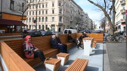 Passanten sitzen an der Bergmannstraße auf Parklets