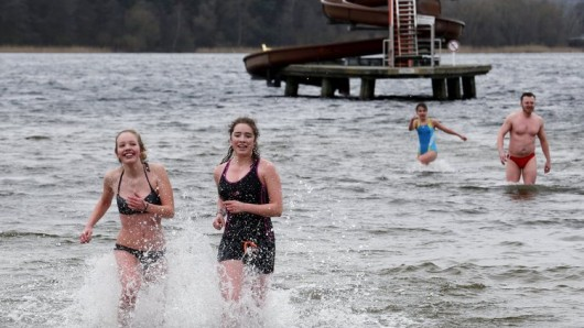 Swimmers wade through cold water during the first opening day at Wannsee lido, a public beach, in Berlin