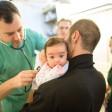 Der Arzt Maximilian Pelzer (l) untersucht am in der Flüchtlingsnotunterkunft im ehemaligen Flughafen Tempelhof im Medical Center ein Flüchtlingskind aus Mazedonien