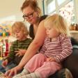 Eine Erzieherin sieht mit Kindern in einer Kita ein Bilderbuch an