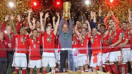 Da ist der Pott - Bayern-Trainer Pep Guardiola stemmt den DFB-Pokal in die Höhe.