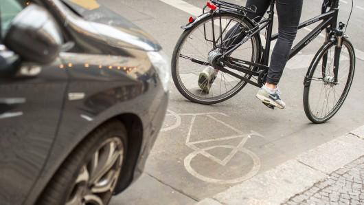Eine Radfahrerin umfährt am 26.05.2016 in Berlin ein auf dem Radweg stehendes Auto. Mit einer Aktionswoche wollen Berliner Polizei und Ordnungsämter ab Montag (30. Mai) gegen Falschparker auf Fahrrad- und Busstreifen vorgehen. Foto: Alexander Heinl/dpa (zu dpa Knöllchenwoche in Berlin - Falschparker im Visier 27.05.2016) +++(c) dpa - Bildfunk+++