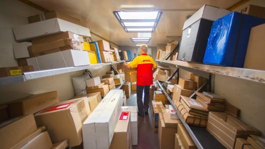 Ein Mitarbeiter des Unternehmens Deutsche Post DHL belädt sein Zustellfahrzeug