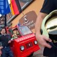 Feuerwehrmann Thomas Gulbe steht vor dem neuen Feuerwehrhaus in Groß Gastrose neben einem alten Feuerwehrauto, an dem die Polen-, Europa-, und Deutschlandfahne wehen.  Im deutsch-polnischen Grenzgebiet teilen sich seither Feuerwehrleute von dies- und jenseits der Neiße in Groß Gastrose (Spree-Neiße) ein gemeinsames Haus