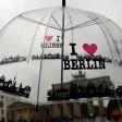 Ein Tourist aus Argentinien schützt sich n Berlin vor dem Brandenburger Tor mit einem Regenschirm vor dem Regen (Archivbild)