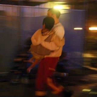 Ein Feuerwehrmann trägt ein aus dem brennenden Haus gerettetes Kind über die Straße