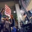 Ein Demonstrant steht am JFK-Airport der Polizei gegenüber