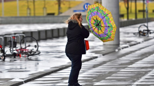 Eine Passantin kämpft  in Berlin mit ihrem Regenschirm