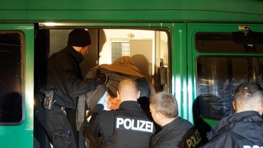 Polizisten führen den mutmaßlichen Geiselnehmer ab