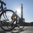 Radfahrer fahren im Sonnenschein an der Siegessäule vorbei