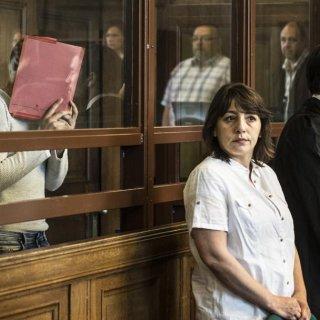 Der Angeklagte Swetoslaw S. verbirgt sein Gesicht, vorne steht seine Frau
