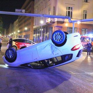 Der BMW kam auf dem Dach zum Liegen, im Hintergrund das Taxi