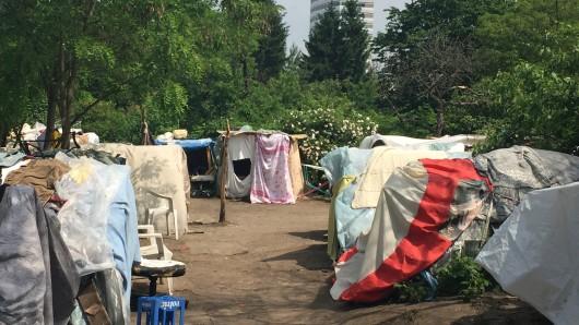 Die Menschen hausen in Zelten aus Planen und Paletten