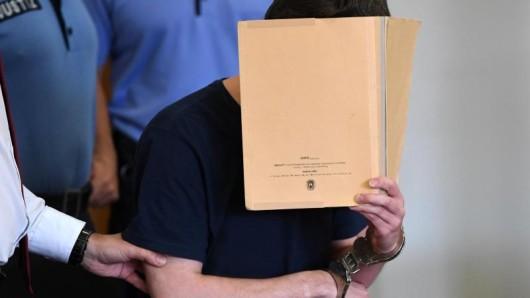 Silvio S. mit einem Aktenordner vor dem Gesicht im Landgericht