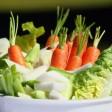 Eine Schüsseln mit Gemüse und Salat steht auf einem Tisch.