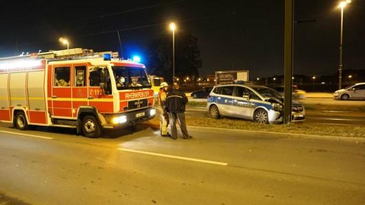 Einsatzkräfte der Feuerwehr stehen neben dem verunglückten Polizeiauto