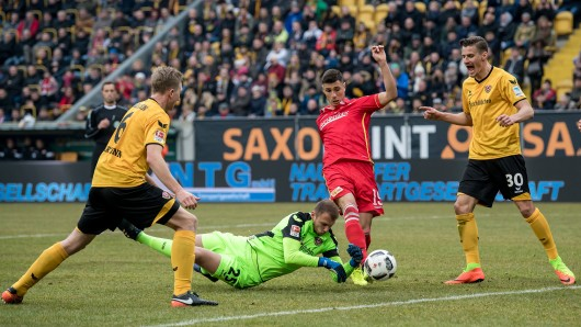 Unions Damir Kreilach (2.v.r.) tritt Dresdens Torwart Marvin Schwäbe den Ball aus den Händen, dessen Mitspieler Marco Hartmann (l.) und Stefan Kutschke schauen zu
