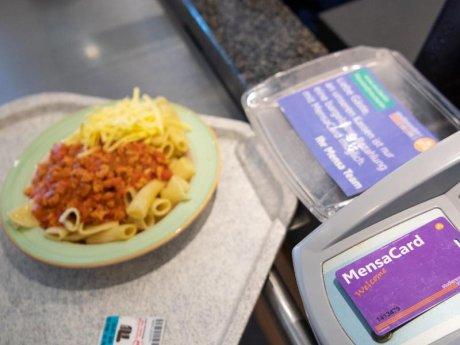 Ein Student bezahlt mit der MensaCard für sein Essen in der veganen Mensa auf dem Campus der TU.