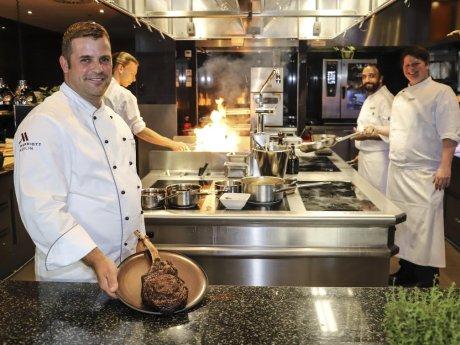 """Grillchef Thomas Czerwionke, präsentiert in der Küche des """"Midtown Grill"""" ein Tomahawk Steak."""