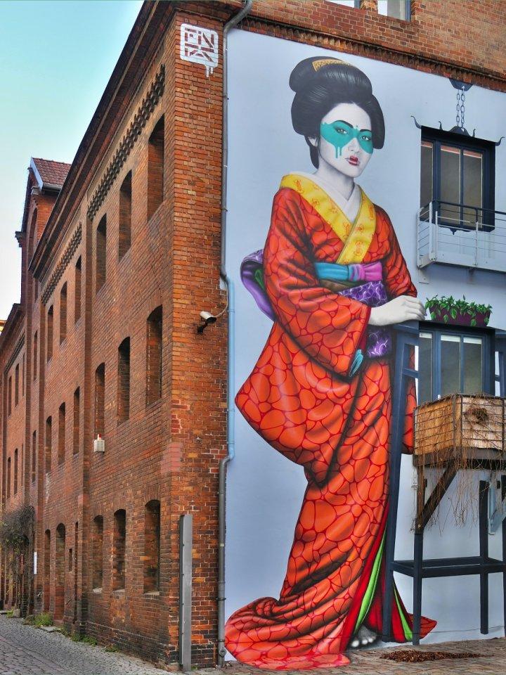 Die mysteriöse Japanerin, die sich an einen Balkon zu lehnen scheint, findet man an der Köpenicker Straße 9 in Kreuzberg.