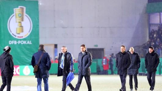 Schiedsrichter Felix Brych (Mitte) bei der Begehung des Platzes