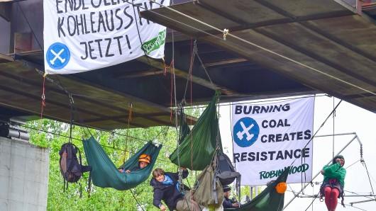 """Umwelt-Aktivisten von """"Ende Gelände"""" und """"Robin Wood"""" liegen in Hängematten unter einer Brücke über Bahngleisen und blockieren somit die Zugverbindung zum Braunkohlekraftwerk in Schwarze Pumpe"""
