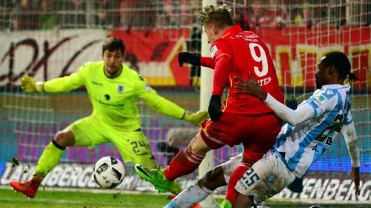 Der Berliner Sebastian Polter (l) und Abdoulaye Ba aus München kämpfen um den Ball