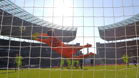 Hertha geht auch in der kommenden Saison im Olympaistadion auf Bundesliga-Torjagd, hier fliegt Augsburgs Torwart Marwin Hitz nach einem Schuss von Vedad Ibisevic (M.)