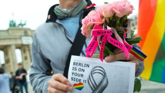Papierstreifen mit der Aufschrift Warum Hass? Wenn es Liebe gibt um Rosen und ein Plakat mit der Aufschrift Berlin is on your Side sind bei einer Trauerveranstaltung für die Opfer von Orlando n Berlin zu sehen